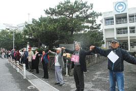 手をつないで市役所を包囲する自衛隊配備反対派の人たち(10日午後)