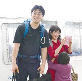 黒島港に到着し、歓迎される吉山医師一家=18日午後、黒島港