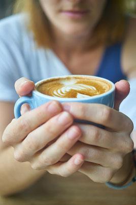 femme-qui-tient-une-tasse-de-cafe-en-premier-plan