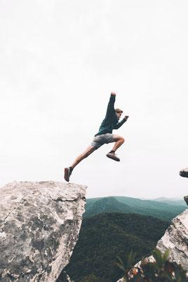Ein sportlicher Mann springt über einen Fels