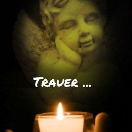 Ein Engel aus Stein mit einer Kerze.