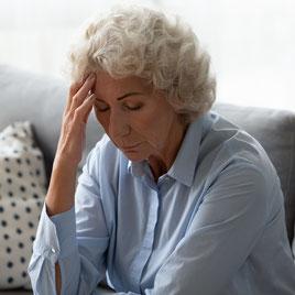 Femme senior appuyant sur la tempe et ayant des difficultés cognitives ou physiques que l'intégration des réflexes archaïques peut améliorer