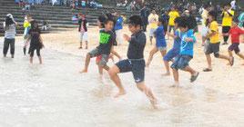 テープカットを合図に、海に飛び込む子どもたち=22日午前、与那国島のナーマ浜