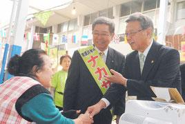 翁長次期知事(右)とともに有権者と握手して回る仲里氏=6日午後、公設市場
