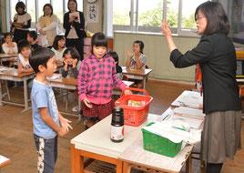 商品がつめ込まれた買い物かごを使い、児童が役割演技を行った=22日、大浜小学校