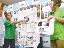 壁新聞を紹介する竹内君(右)と石田君=21日、竹富町役場