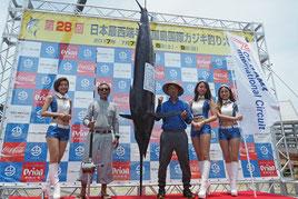 最終日トップ、150㌔のクロカワを釣り上げた上間徳三郎さん(左から2人目)=9日午後、久部良漁港