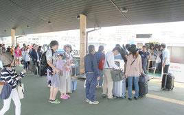 沖に避難したフェリーを降り、荷物を受け取る人たち(手前)と乗船を待つ列(奥)=20日午後、石垣港離島ターミナル