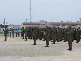 1周年記念式典で一斉に敬礼する隊員ら=23日、駐屯地内広場