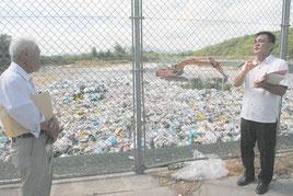 ごみ埋め立てが進む一般廃棄物最終処分場で、委員にごみ処理の現状を説明する市職員(右)。現在、プラスチック類は埋め立て処理されている=6月30日午後