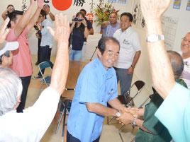 当確の知らせを受け、支持者と握手する西大舛氏。何度も万歳の声が響いた=8月29日、選対事務所