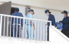 事件のあった部屋を調べる捜査員ら=2日午前、石垣市新川