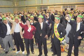 総決起集会でガンバロー三唱する仲里氏(右から2番目)と支持者=6日夜、屋内練習場