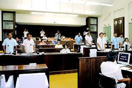 県民大会の会場変更を求める決議の採決。起立して賛成しているのが与党=7日午前