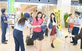 観光客らにチラシを配布して密輸防止の協力を呼びかける税関職員ら=2日午後、石垣空港