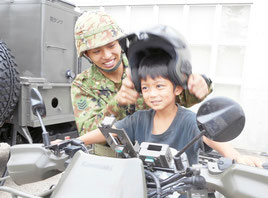 偵察用バイクの乗車体験で、子どもにヘルメットをかぶせる自衛隊員=26日午後、市屋内練習場
