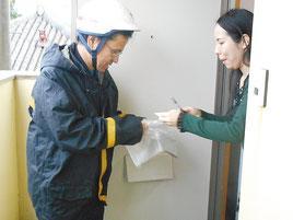 マイナンバーの通知カードを配達する八重山郵便局員(4日午前)
