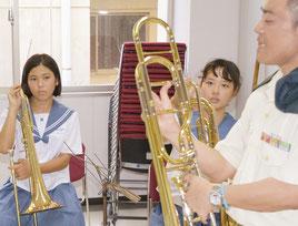 音楽隊からトロンボーンの説明を受け、真剣な表情で見つめる生徒=16日、石垣市総合体育館研修室