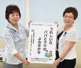 當山会長(左)から石垣教育長にタペストリが贈られた=2日、市教委