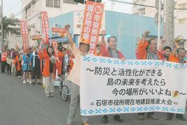 市役所の現地建て替えを求めてデモ行進する人たち=10日午後、美崎町