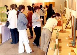 熱心に八重山上布を観賞する来場者ら=17日、市民会館展示ホール