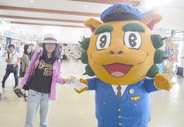 「シーサーやいま」からチラシを受け取る観光客(左)=18日午前、石垣港離島ターミナル