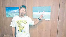 自身の作品の前でコンドイ浜の魅力を語る上勢頭輝さん=3日、竹富島ゆがふ館内テードゥンギャラリー