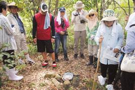 沖縄戦当時の食器が残るかまど跡に見入る参加者(20日午前)
