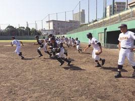 守備練習を中心に汗を流す八重高ナイン=23日午後、鹿児島市鴻池公園野球場