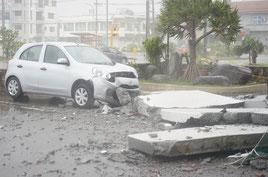 5階建てホテルの建物から落下した外壁とフロント部分が大破した車両=7日午後、石垣市八島町