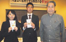 琉大医学部に合格した長谷部、高橋さんを激励する宮平会長(20日夜)
