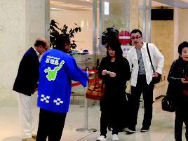チャーター便の乗客にちんすこうを配る市観光交流協会のメンバー=10日午前、南ぬ島石垣空港