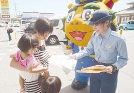 相談案内のチラシを配る當山警務係長(右)と受け取る市民=11日午前、サンエー石垣シティ