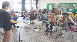 練習に励む石垣フィルハーモニー管弦楽団の団員ら=23日午後、県立石垣青少年の家