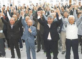 前津氏の出馬表明会見後、ガンバロー三唱で気勢を上げる前津氏と支援者=19日午後、大川公民館