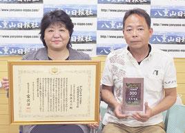 27日東京で表彰を受けたことを報告した長濱光江会長(左)と喜屋武松信代表(右)=1日午後、八重山日報社