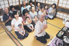 文之さんを筆頭に、仏壇に手を合わせて先祖に感謝する大盛さん一家。今年は一族に子どもが3人誕生し、笑顔が絶えない=26日夜、石垣市真栄里