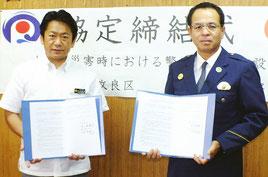 大規模災害における代替施設協定調印した(左から)中山市長、仲村署長=18日午後、市役所