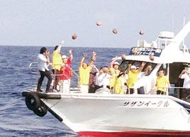 恋路ヶ浜に無事に届くことを願い、一斉にやしの実を投げ入れる参加者たち=19日午前、鳩間島沖(提供写真)
