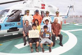 家族と一緒に式典に参加した由羅くん(前列左)と、S―76D型ヘリ「おきあじさし」(第11管区海上保安本部提供)