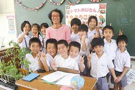 本村シュウさんが海星小2年生児童にミニトマトの苗などを贈呈した=17日午前、海星小学校