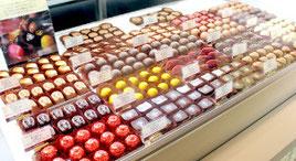 「デイゴ」、「紅イモ」、「ヒラミレモン」など沖縄テイストの高級チョコが並ぶ=24日、エーデルワイス沖縄本店