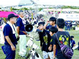 望遠鏡をのぞき込む参加者たち=6日、南ぬ浜町緑地公園