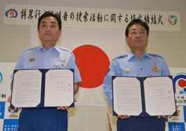 協定書に署名した宇根消防長(左)と与那嶺署長=14日、八重山署