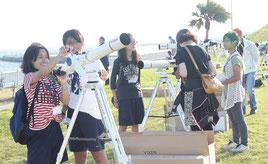 会場に設置された天体望遠鏡を使う来場者たち=15日夕、南ぬ浜町緑地公園