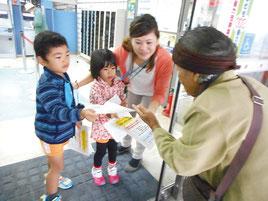 園児たちがお年寄りに「詐欺に気をつけて」とチラシを差し出した=15日午前、琉球銀行八重山支店