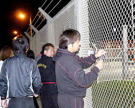 米軍フェンスの異物を取り除く住民ら=15日夜、米軍キャンプ・シュワブゲート前=名護市辺野古