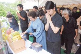平和への願いを込めて手を合わせる全戦没者追悼式・平和祈念式の参列者=23日午後、八重守之塔前
