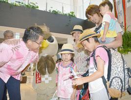 レセプションで歓迎された坂本さん家族。琉駕君(右手前)は飛行機の模型を受け取り、「飾って遊ぶ」とはしゃいだ=1日、石垣空港