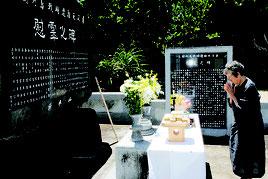 尖閣列島戦時遭難者慰霊碑に手を合わせる慰霊祭参列者=3日午後